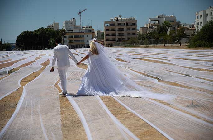 couple-walking-awat-from-camera-with-veil-on-the-ground.jpg