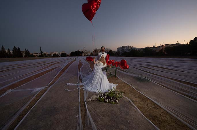 wedding-couple-in-the-middle-of-the-field-with-veil-laid-out.jpg